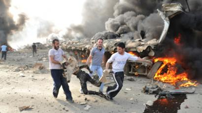 People run carrying a burnt body at the site of an explosion in Damascus May 10, 2012 (Reuters / Sana / Handout)