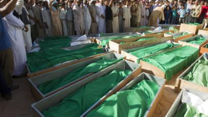 People stand around the coffins of 28 people, who Libyan government officials say were killed after their houses were bombed by NATO forces, in Majar, south of Zlitan, 160 km (99 miles) east of Tripoli, August 9, 2011. (Reuters / Caren Firouz)