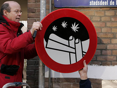 Employees put a sign forbidding people to smoke cannabis. (AFP Photo / Marcel Antonisse)