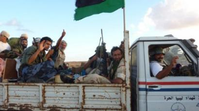Libya's National Transitional Council (NTC) fighters celebrate after capturing the key Red Valley on the road to Moamer Kadhafi's hometown of Sirte on September 8, 2011 on their way to reinforce the frontline. The Red Valley area, 60 kms (40 miles) east of Sirte, was one of the main lines of defence of pro-Kadhafi troops. (AFP Photo/Herve Bar)