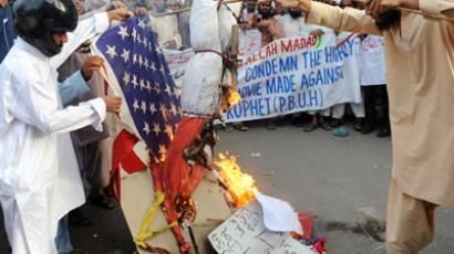 Pakistani Sunni Muslim protesters torch a US flag and an effigy of the US President Barack Obama during a protest rally against an anti-Islam movie in Karachi on September 16, 2012. (AFP Photo/Rizwan Tabassum)