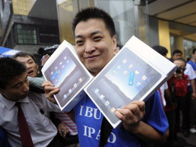 Apple customer Han Ziwen holds up his ipads outside a Apple's flagship store in Beijing after queueing for 60 hours. (AFP Photo / Peter Parks)