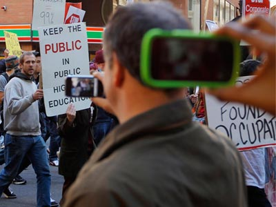 Onlookers take photographs with their phones as members of the Occupy Boston movement are joined by students from local colleges and universities demonstrating against the cost of education in downtown Boston (Reuters/Brian Snyder)