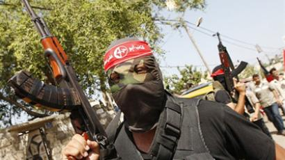 Masked Popular Front for the Liberation of Palestine (PFLP) militants hold up their weapons during the funeral of Bassam Badwun in Gaza City (AFP Photo / Said Khatib)