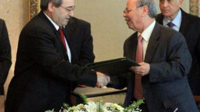 Syrian Deputy Foreign Minister Faisal Meqdad (L) shakes hands with Arab League deputy secretary general Ahmed bin Hilly (R) after signing an agreement during a meeting attended by Arab League Secretary General Nabil al-Arabi (back-R) at the institution's headquarters in Cairo on December 19, 2011 as Syria finally agreed to cooperate with Arab observers (AFP Photo / Khaled Desouki)