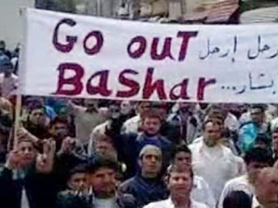 """Syria, Tal Kalakh: An image grab taken from a YouTube video shows anti-government protesters holding a banner that reads in Arabic and English """"Go out Bashar"""" during a pro-democracy demonstration after Friday prayers in Tal Kalakh on June 10, 2011. (AFP Photo / Youtube)"""