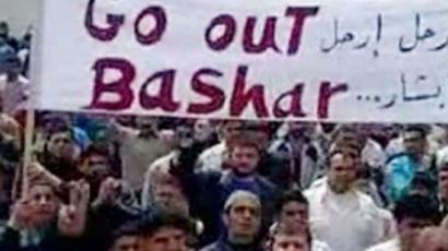 "Syria, Tal Kalakh: An image grab taken from a YouTube video shows anti-government protesters holding a banner that reads in Arabic and English ""Go out Bashar"" during a pro-democracy demonstration after Friday prayers in Tal Kalakh on June 10, 2011. (AFP Photo / Youtube)"