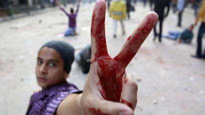 A protester flashes a victory sign with his bloodied hand as other protesters throw stones at army soldiers at the cabinet near Tahrir Square in Cairo December 16, 2011 (Reuters/Amr Abdallah Dalsh)