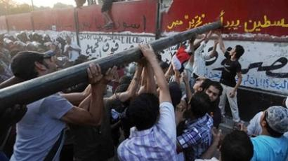 Cairo: Egyptian demonstrators use a large metal bar on September 9, 2011 as they try to demolish a wall recently built outside the Israeli embassy in Cairo to protect the building. (AFP Photo / Mohamed Hossam)
