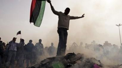 "A Libyan protester stands on top of a pile of burning ""Green Books"" during a protest against Libyan leader Moammar Gadhafi during a demonstration against him in Benghazi, eastern Libya, Wednesday, March 2 , 2011"