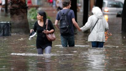 People wade through a flooded street after heavy rain in a Buenos Aires neighbourhood, December 6, 2012 (Reuters / Enrique Marcarian)