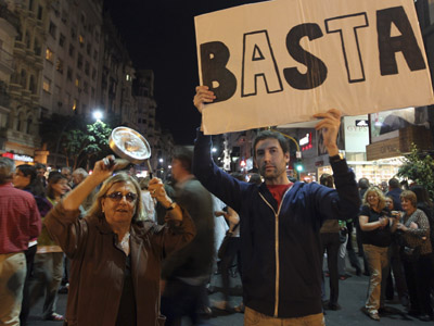 "A protester bangs a pan as another holds a placard that reads ""Enough"" while shouting slogans against the government of Argentine President Cristina Fernandez de Kirchner in Buenos Aires September 13, 2012. (Reuters/Enrique Marcarian)"