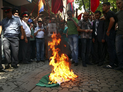 Protesters burn a Hungarian national flag during a rally outside the Hungarian consulate in Yerevan, September 1, 2012. (Reuters/Tigran Mehrabyan/PanARMENIAN Photo/Handout)