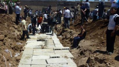 A handout picture released by the Syrian opposition's Shaam News Network shows people watching the mass burial on May 26, 2012 (AFP Photo/HO?Shaam News Network)
