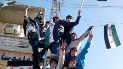 Syrians climb a pole and hold flags during a protest against Syria's President Bashar Al-Assad in Kafranbel near Idlib. (	REUTERS/Handout)