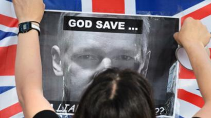 London: A supporter of Wikileaks founder Julian Assange pastes up a protrait of Assange onto a Union Flag outside the Supreme Court in central London on May 30, 2012. (AFP Photo / Leon Neal)