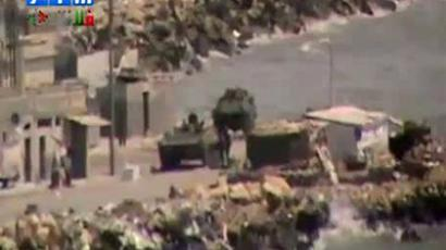 Syria, Latakia: An image grab taken from a video uploaded on YouTube shows what appears to be a Syrian armoured vehicles stationed along the coast road in a residential area of the country's main Mediterranean port city Latakia on August 14, 2011 (AFP photo)