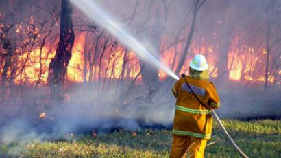 This undated handout picture provided by New South Wales Rural Fire Service (NSW Rural Fire Service) on January 8, 2013 shows a NSW Rural Fire Service worker spraying water on a bush fire at Green Point in New South Wales. (AFP Photo/ NSW Rural Fire Service)