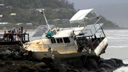 People look at a boat that has been washed up onto rocks at Airlie Beach located around 120 km (75 miles) south-east of the city of Townsville in Queensland January 25, 2013. Heavy rains - the remnants of Tropical Storm Oswald - caused some major highways and dozens of roads to be cut off, isolating towns and flooding properties, according to local authorities. (Reuters/Bon Fenney)