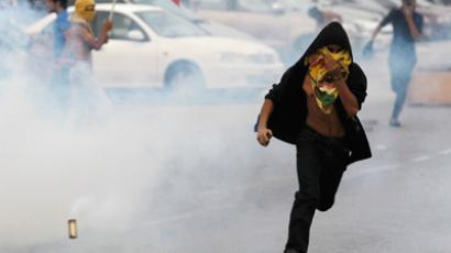 A protester runs away from tear gas released by riot police during clashes after the rally by Bahrain's main opposition party Al Wefaq in Budaiya, west of Manama, April 20, 2012 (Reuters / Hamad I Mohammed)