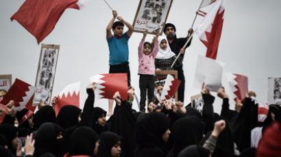 Bahraini Shiite Muslims wave their national flags and shout slogans during an anti-government protest in the Manama coastal suburb of Karbabad on December 28, 2012 (AFP Photo / Mohammed Al-Shaikh)