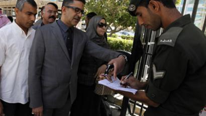 Ghassan al Daif (C), a consultant at Salmaniya Medical Hospital, speaks to security officials at the gate to the court compound, as he arrives for his hearing in Manama March 5, 2012. (Reuters/Hamad I Mohammed)