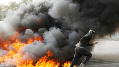 An anti-government protester runs for cover after setting fire to tyres, in Budaiya, west of Manama, early April 22, 2012 (Reuters/Hamad I Mohammed)