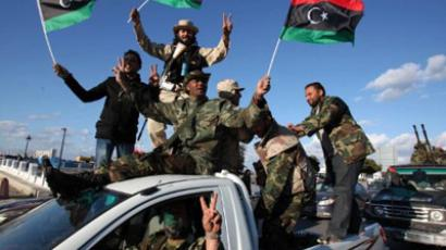 Waving the newly adopted flag, members of the new Libyan military force under the ruling National Transitional Council parade along a main street in the Libyan capital Tripoli on February 14, 2012. (AFP Photo/Mahmud Turkia)