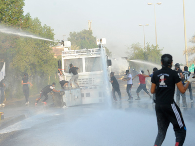 Anti-government protesters attack a riot police water cannon tanker as they march towards Pearl Square after visiting the grave of Mohammed Ali Moshaima in the village of Jidhafs, west of Manama, October 5, 2012 (Reuters / Stringer)