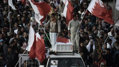 Bahraini Shiite Muslims hold national flags on the top of a van during the funeral of Habib Ebrahim Abdullah on January 13, 2013.(AFP Photo / Mohammed Al-Shaikh)