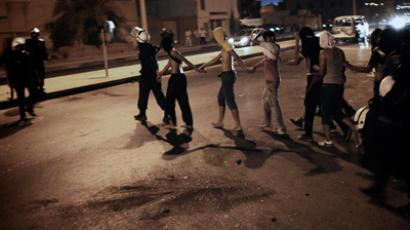 Bahraini policemen arrest protestors during an anti-government demonstration in the village of Bani Jamrah, West of Manama, on August 2, 2012 (AFP Photo / Mohammed Al-Shaikh)