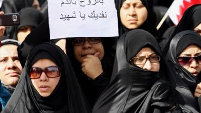 "A Bahraini Shiite woman holds a signs that reads in Arabic ""We sacrifice our souls and blood for martyrs""  February 18, 2011 (AFP Photo / Str)"