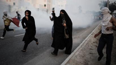 Bahraini protestors run for cover from tear gas fired by riot police following an anti-government rally to demand political reforms on February 12, 2013.(AFP Photo / Mohammed Al-Shaikh)