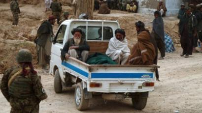 In a photograph taken on March 11, 2012, Afghan villagers sit in vehicles as they prepare to remove the victims of a shooting from homes in the village of Alkozai in Kandahar Province (AFP Photo / Jangir)