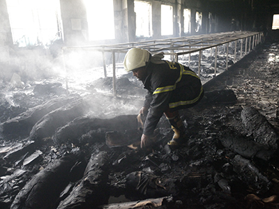 A firefighter inspects a garment factory after a devastating fire in Savar November 25, 2012. (Reuters / Andrew Biraj)