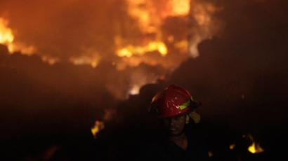 A firefighter tries to control a fire at a garment factory in Savar, outskirts of Dhaka November 24, 2012 (Reuters / Andrew Biraj)