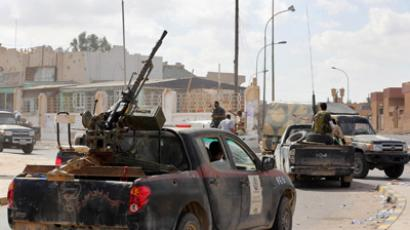 Libyan pro-government forces drive through the streets of Bani Walid on October 24, 2012 after seizing control of the city, one of the last bastions of Moamer Kadhafi's ousted regime (AFP Photo / Mahmud Turkia)