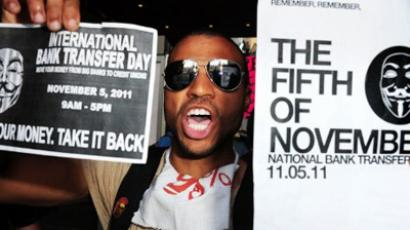 An Occupy protestor holds signs calling for citizens to close their bank accounts at big banks and move their money to credit unions in Hollywood, California November 2, 2011 (AFP Photo / Robyn Beck)