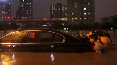 Residents push a stranded car on a flooded street amid heavy rainfalls in Beijing, July 21, 2012 (Reuters / Stringer)