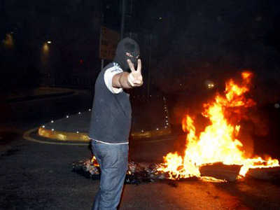 A hooded man flashes the V-sign for victory during overnight clashes in Beirut on May 21, 2012 (AFP Photo/Str)