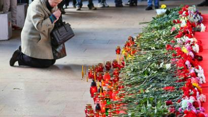 A resident of Minsk lays flowers in tribute of the explosion victims. (RIA Novosti / Sergey Samokhin)