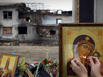 An Ossetian woman lights a candle in front of an icon at the gymnasium of the destroyed school in Beslan, 10 September 2004. (AFP Photo / Maxim Marmur)