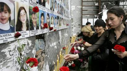 People lay flowers and light candles inside the Beslan school gymnasium (AFP Photo / Kazbek Basayev)