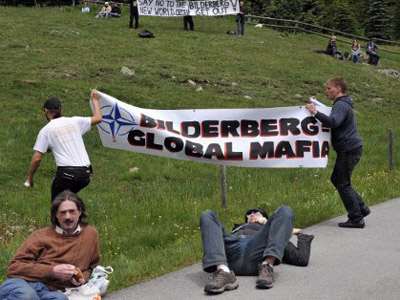 Activists protest close to the Suvretta House five-star hotel in the chic Swiss ski station of St Moritz, where the Bilderberg Group is holding its annual meeting on June 9, 2011. (AFP Photo / Fabrice Coffrini)