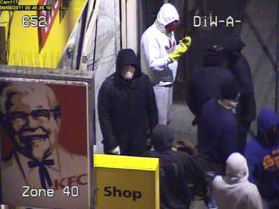 An image taken from a CCTV camera released by the Metropolitan police on August 9, 2011 shows masked rioters standing by a smashed shop in West Northwood in London during rioting late last night (AFP Photo / Metropolitan Police)