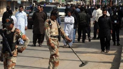 A Pakistani paramilitary soldier uses a metal detector along the roadside during a Shiite Muslim religious procession on the ninth day of holy month of Moharram in Karachi on November 24, 2012.