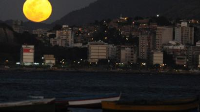 The full moon rises over Rio de Janeiro on August 31, 2012. (AFP Photo/Vanderlei Almeida)