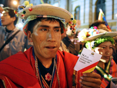 An Aymara native shows the new Constitution (AFP Photo / Aizar Raldes)
