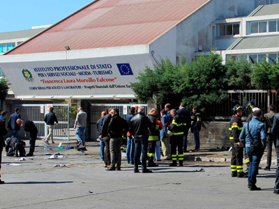 Italian policemen and fire fighters inspect in front of the school where a bomb exploded in the southern Italian town of Brindisi May 19, 2012 (Reuters / ANSA)
