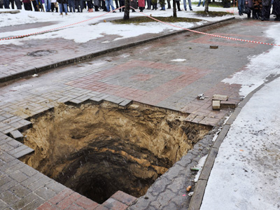 Mother and her child fall in hole in Bryansk. (RIA Novosti/Nikolay Pahomov)